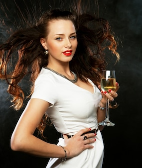 Donna sorridente in abito da sera con un bicchiere di spumante