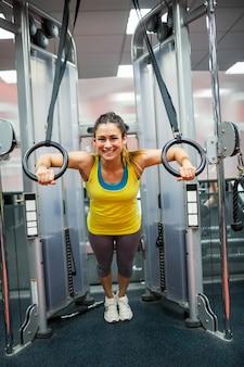 Donna sorridente che esercita le braccia