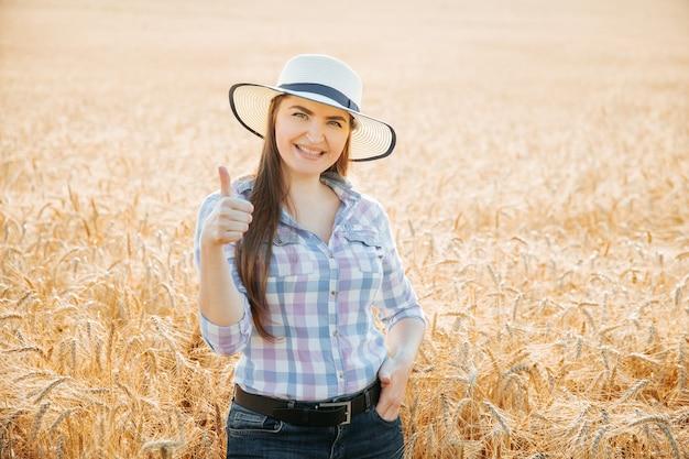 Contadina sorridente con cappello che mostra pollice in su e guarda la telecamera in piedi su un terreno agricolo femmina sorridente...