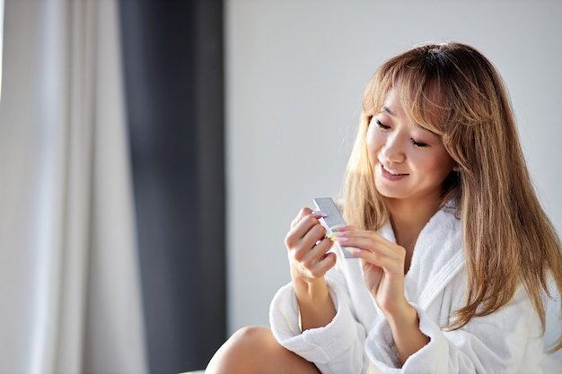 Donna sorridente limita le unghie con una lima mentre è seduta sul letto in accappatoio a casa, si prende cura di se stessa, concetto di bellezza.