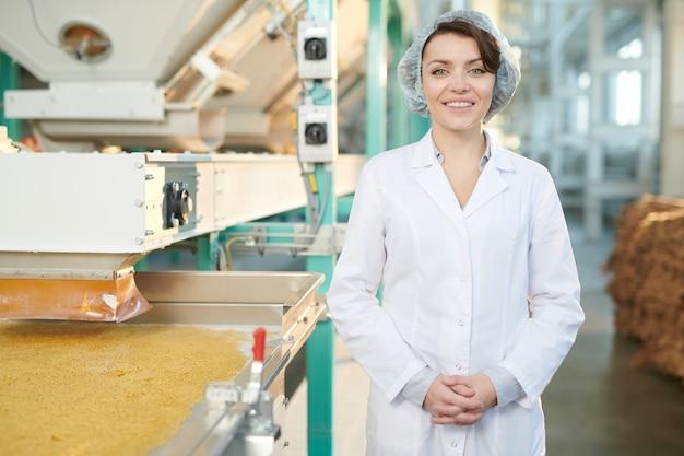 Donna sorridente in fabbrica alimentare