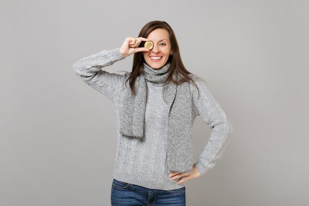 Donna sorridente in maglione grigio, sciarpa che copre l'occhio con bitcoin, valuta futura isolata su sfondo grigio muro. stile di vita sano, emozioni delle persone, concetto di stagione fredda. mock up copia spazio.