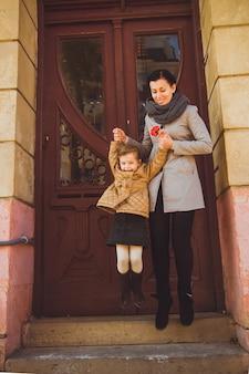 Donna sorridente in trincea grigia che salta con sua figlia dalle scale relazioni familiari