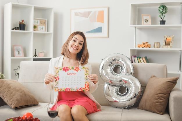 Donna sorridente il giorno della donna felice tenendo il calendario seduto sul divano in soggiorno