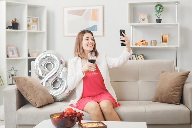 Donna sorridente in una felice festa della donna con in mano un bicchiere di vino e scatta un selfie seduta sul divano in soggiorno