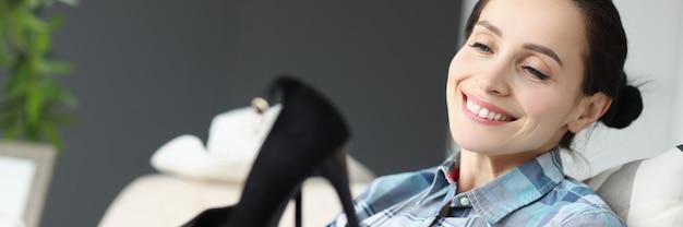 La donna sorridente che tiene le scarpe nere mentre è seduta sul divano la scelta delle donne è il concetto di scarpe