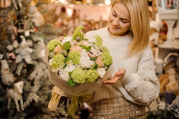 Donna sorridente che tiene un mazzo di ortensie verdi tenere e fiori bianchi