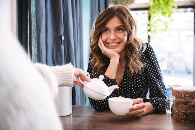 Donna sorridente che tiene tazza mentre barista versando il tè al bancone del caffè