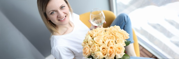 Donna sorridente con in mano un bicchiere di vino e un mazzo di fiori