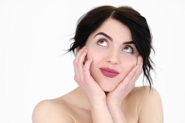 Donna sorridente tenendo la testa tra le mani e alzando lo sguardo sul muro bianco.