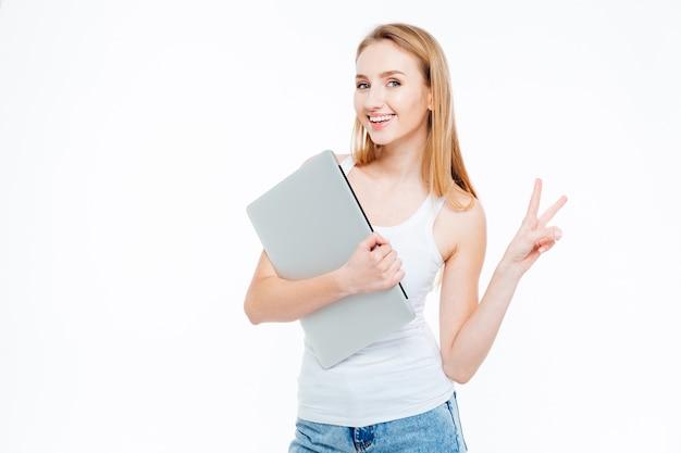 Donna sorridente che tiene in mano un computer portatile e mostra un segno di due dita isolato su uno sfondo bianco