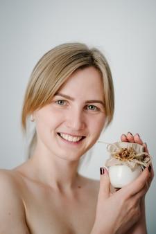 Donna sorridente che tiene piccolo vasetto di crema per la pelle e applicazione di lozione per bottiglie, cosmetici naturali.