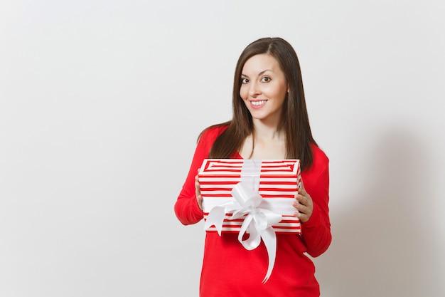 Donna sorridente che tiene la scatola attuale a strisce rossa con il nastro, arco isolato su fondo bianco. per la pubblicità. san valentino, giornata internazionale della donna, natale, compleanno, concetto di vacanza.