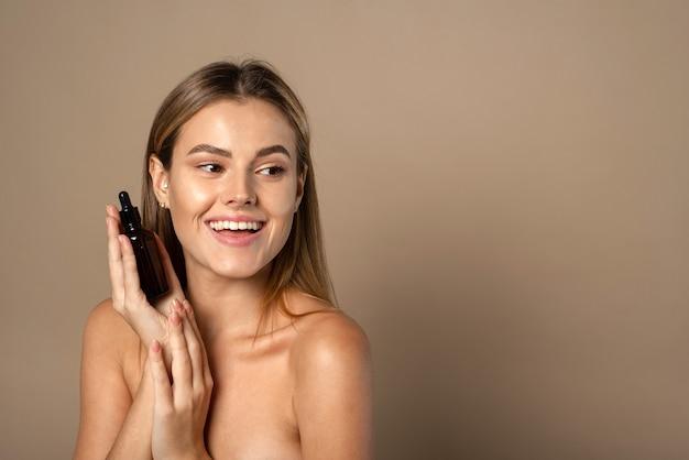 Donna sorridente che tiene il siero di vitamina c vicino al viso su sfondo beige. cura della pelle e concetto di salute.