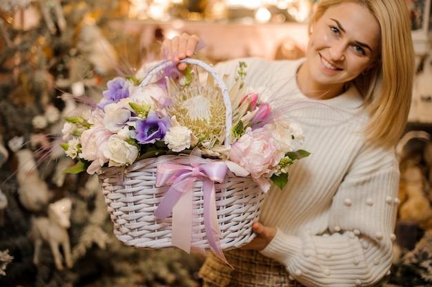 Donna sorridente che tiene un cesto di vimini di teneri fiori bianchi, rosa e viola