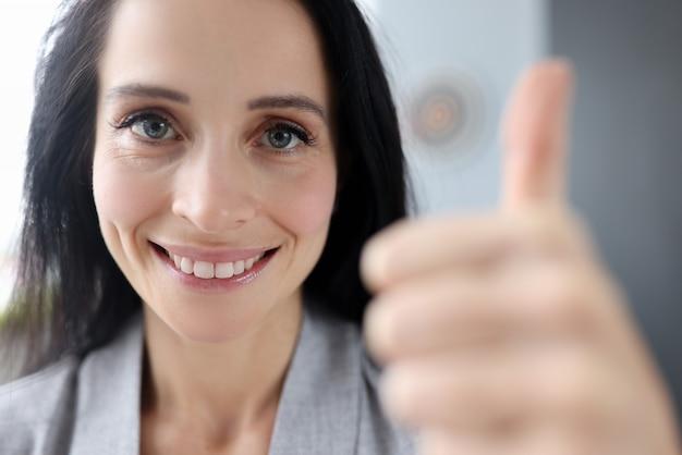 La donna sorridente tiene i suoi pollici in su. proposte di affari di successo e concetto di investimento
