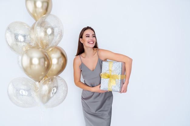 La donna sorridente tiene in mano grandi scatole regalo avvolte vicino a mongolfiere arrivate alla celebrazione della festa