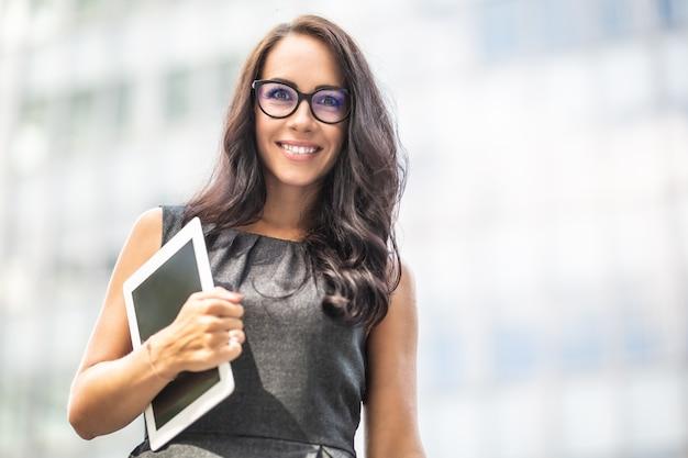 La donna sorridente tiene un tablet sorridente, camminando in abiti da lavoro fuori dall'edificio degli uffici.