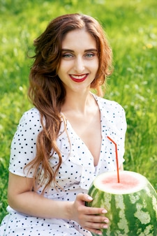 La donna sorridente tiene l'anguria su erba