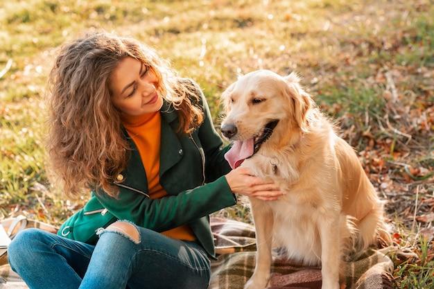 Donna sorridente che abbraccia il suo cane golden retriever vicino al viso. golden retriever cane che gioca con una donna riccia che cammina all'aperto giornata di sole. amore e cura per l'animale domestico.