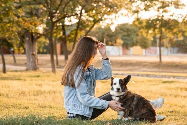 Donna sorridente che abbraccia il suo cane welsh corgi. cane welsh corgi che gioca con una donna che cammina all'aperto in una giornata di sole, amore e cura per l'animale domestico.