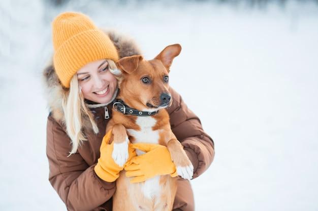 Donna sorridente che abbraccia cane bastardo rosso nella foresta di inverno.