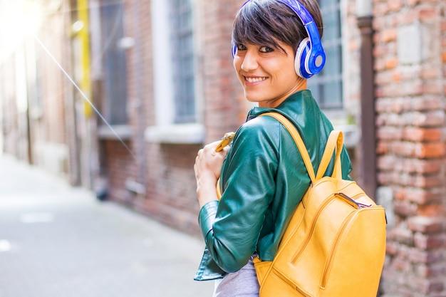 La donna sorridente sta ascoltando musica con le cuffie head