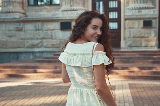 Donna sorridente che guarda lontano sopra la spalla mentre si cammina outdor