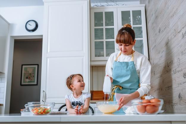 Una donna sorridente guarda sua madre, che sta battendo l'impasto con un mixer