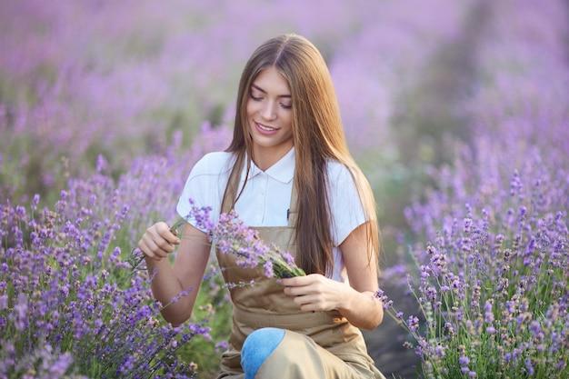Donna sorridente che fa il mazzo nel campo di lavanda Foto Premium