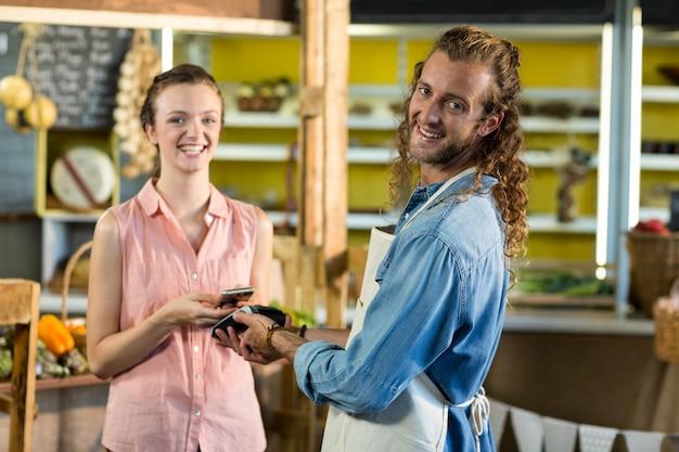 Donna sorridente che effettua un pagamento utilizzando la tecnologia nfc