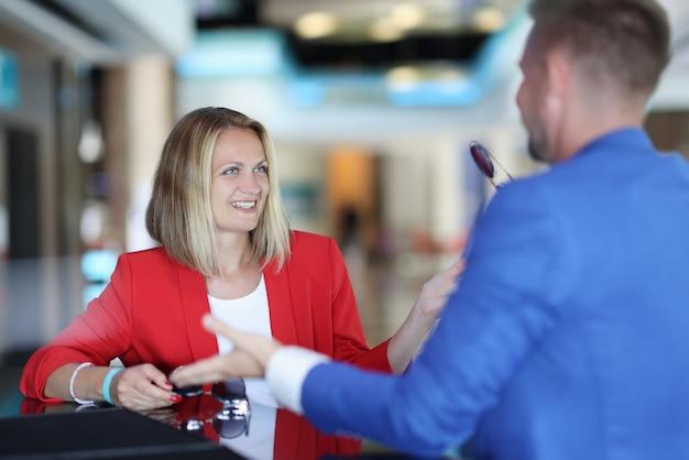 Donna sorridente e uomo che parla al bancone del bar
