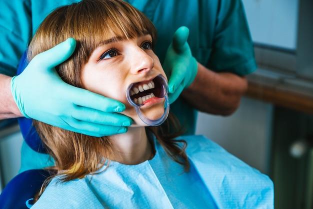 Bocca di donna sorridente in trattamento presso la clinica odontoiatrica Foto Premium
