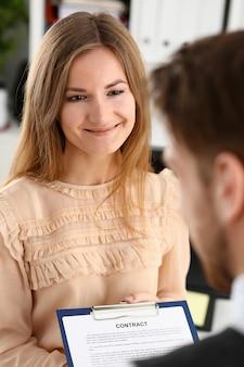 La donna sorridente offre il modulo del contratto sul blocco degli appunti e sulla penna d'argento per firmare il primo piano
