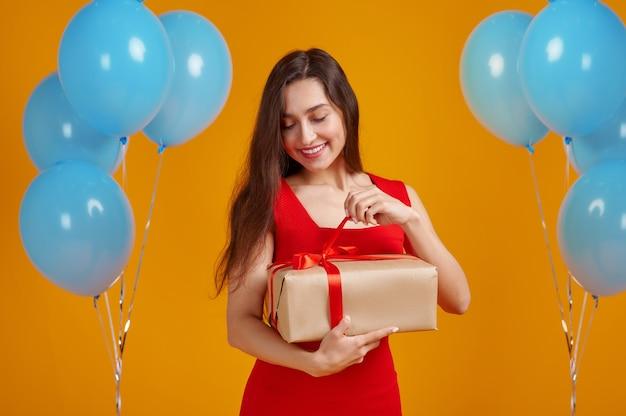 La donna sorridente apre la confezione regalo con nastri rossi. la bella persona femminile ha ricevuto una sorpresa, un evento o una festa di compleanno, una decorazione di palloncini