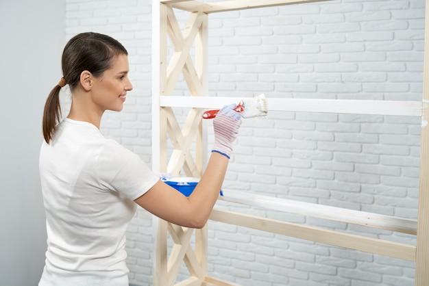 Donna sorridente che dipinge una rastrelliera in legno di colore bianco