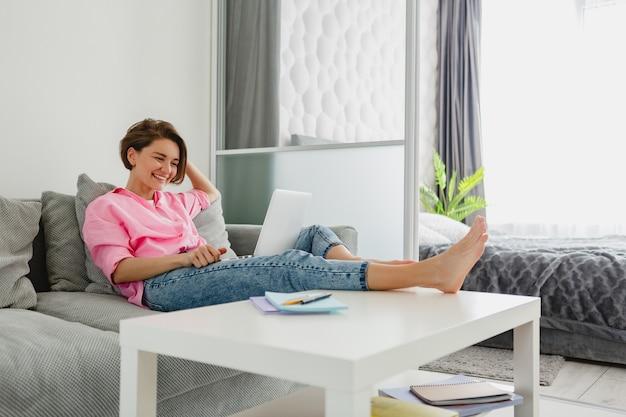 Donna sorridente in camicia rosa seduto rilassato sul divano a casa a tavola lavorando online su laptop da casa