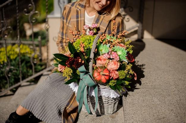 Donna sorridente in cappotto plaid seduto su scale di cemento con un cesto di vimini di fiori
