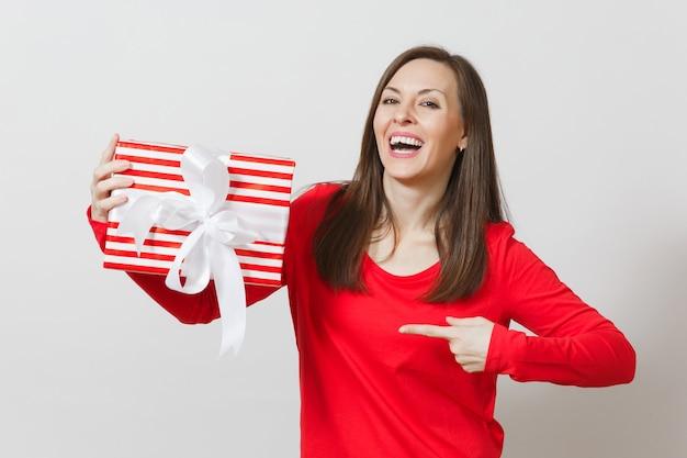 Donna sorridente che indica sulla scatola attuale a strisce rossa con il nastro isolato su fondo bianco. per la pubblicità. san valentino, giornata internazionale della donna, natale, compleanno, concetto di vacanza.
