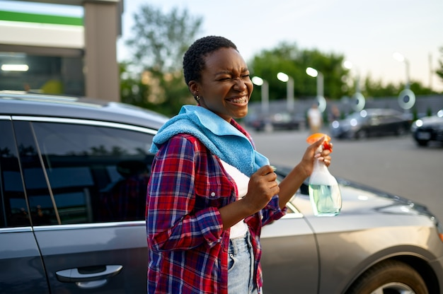 Donna sorridente posa con spray lavavetri e uno straccio, stazione di lavaggio auto a mano. industria o attività dell'autolavaggio. la persona di sesso femminile pulisce il suo veicolo dallo sporco all'aperto