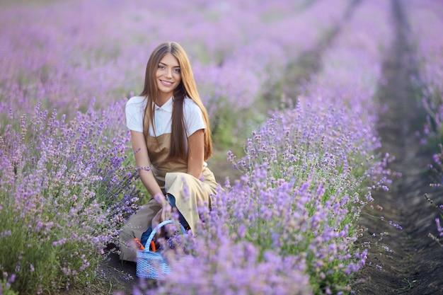 Donna sorridente in posa con cesto in campo di lavanda lavender