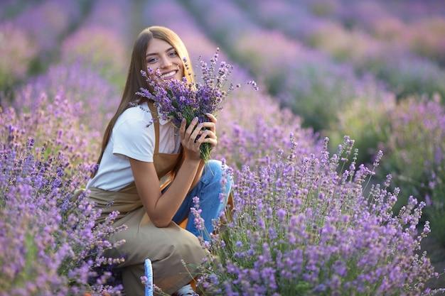 Donna sorridente in posa con bouquet in un campo di lavanda