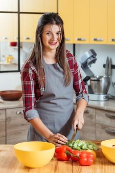 Donna sorridente che prepara le verdure nella cucina