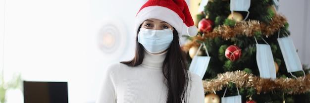 La donna sorridente nella mascherina medica protettiva sta accanto all'albero di natale e tiene il regalo.