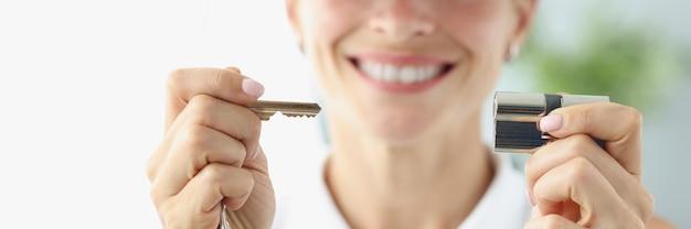 Donna sorridente in berretto rosso che tiene la chiave e il primo piano del buco della serratura