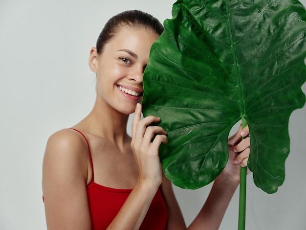 Donna sorridente in costume da bagno rosso foglia verde isolato sfondo