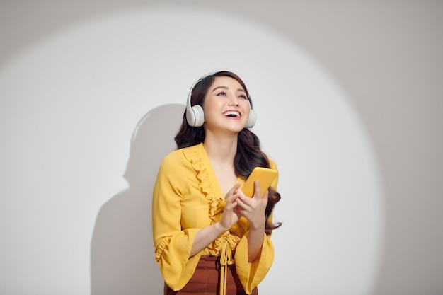 Donna sorridente in un momento di relax a casa, sta riproducendo musica utilizzando uno smartphone