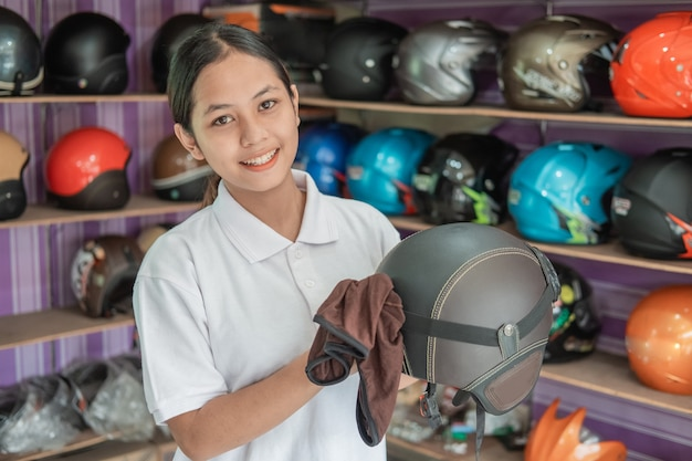 Sorridente donna assistente di negozio pulizia casco con un panno nel negozio di casco