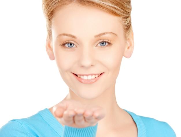Donna sorridente che mostra qualcosa sul palmo della mano