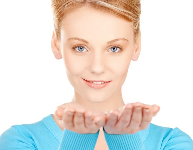 Donna sorridente che mostra qualcosa sui palmi delle mani